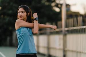 jovem atleta asiática feminina, estendendo-se depois de uma corrida ao ar livre