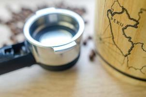 grãos de café com copo e barril na mesa de madeira foto