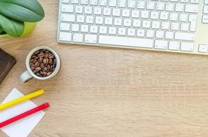 local de trabalho com teclado na mesa de madeira foto