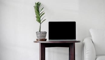 laptop de tela preta na parede branca mínima foto