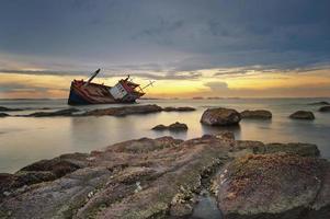 barco naufragado ao pôr do sol foto