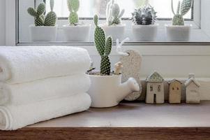 toalhas limpas dobradas com planta de casa no balcão de madeira foto