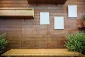 banco contra a parede de madeira com molduras em branco e prateleira foto