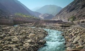 rio que flui ao longo da cordilheira de karakoram no verão foto