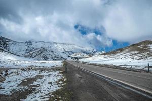 uma estrada em meio a montanhas cobertas de neve foto