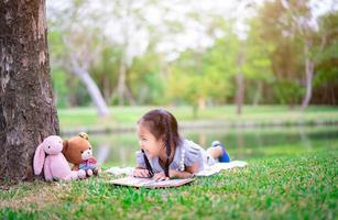 jovem menina asiática com livro e bichos de pelúcia no parque