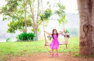 jovem menina asiática em balanço de árvore foto