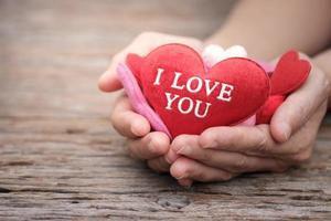 mãos segurando um travesseiro em forma de coração foto
