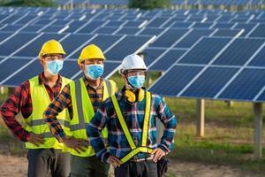 trabalhadores mascarados ao lado de painéis solares
