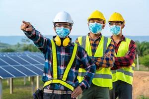 trabalhadores mascarados ao lado do painel solar