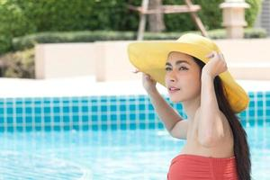 mulher asiática usando um chapéu amarelo na piscina