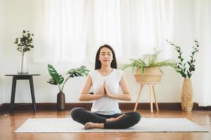 mulher asiática fazendo yoga meditação em casa