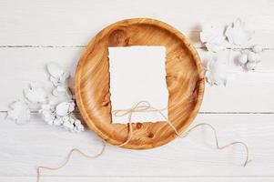 papel em branco na tigela de madeira na mesa de madeira