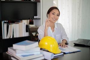 mulher asiática com capacete e prancheta no escritório foto