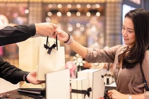 assistente de loja entregando sacola de compras ao cliente