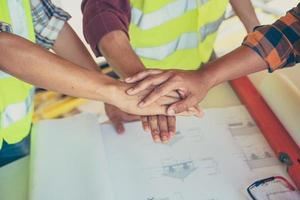 três homens juntam as mãos