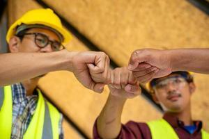 três homens colocando os punhos juntos