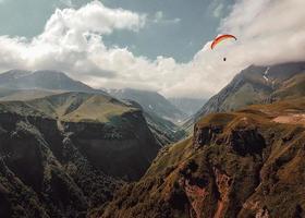 pessoa parapente sobre montanhas