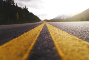 estrada amarela e preta sob árvores verdes e nuvens brancas foto