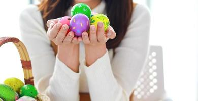 mulher segurando ovos de páscoa coloridos