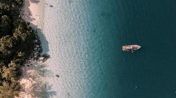 Vista aérea do barco no oceano perto de uma praia