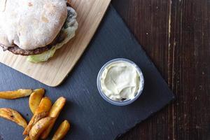 hambúrguer de churrasco com batatas fritas e molho
