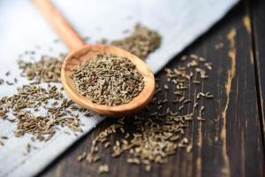 sementes de cominho na colher de pau foto