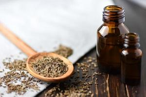 sementes de cominho e óleo em garrafas