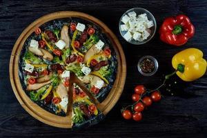 pizza de massa preta com legumes e queijo