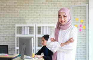 mulher muçulmana e amigo no escritório moderno foto