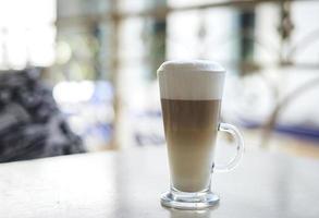 café com leite em caneca clara na mesa foto