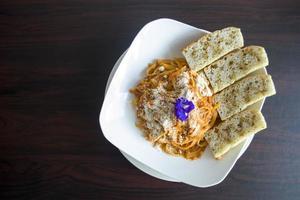 prato de macarrão com pão fatiado foto