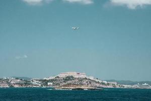 avião branco sobrevoando uma cidade