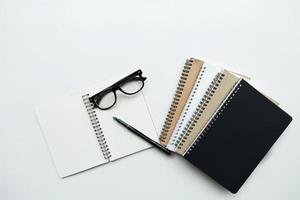 cadernos com caneta e óculos