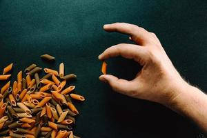 mão segurando um pedaço de macarrão com outro macarrão foto
