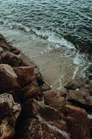 água batendo contra pedras e areia foto