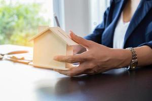 mulher segurando casa de madeira