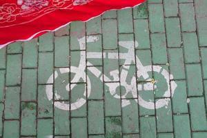 placa de estrada para bicicleta pintada em tijolos verdes foto