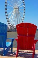 cadeiras coloridas em um cais com roda gigante no fundo.