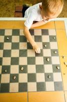 criança jogando damas ou jogo de tabuleiro de damas ao ar livre foto