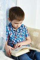 menino lendo livro foto