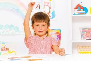 menino mostrando o flashcard da carta na aula de leitura foto