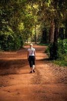 mulher caminhando na estrada rural foto