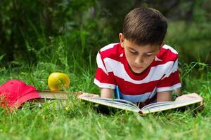 menino lendo um livro na grama foto
