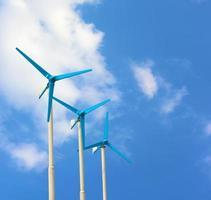 três turbinas eólicas gerando eletricidade no céu azul