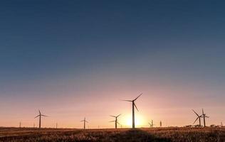 silhueta de um moinho de vento em um campo rural ao pôr do sol