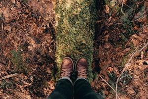 pessoa de pé em um tronco coberto de musgo foto