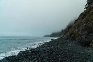litoral e montanha sob céu nublado foto