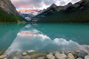 um lago perto de uma montanha verde sob nuvens brancas foto