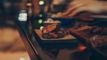 carne cozida em uma tábua de madeira marrom
